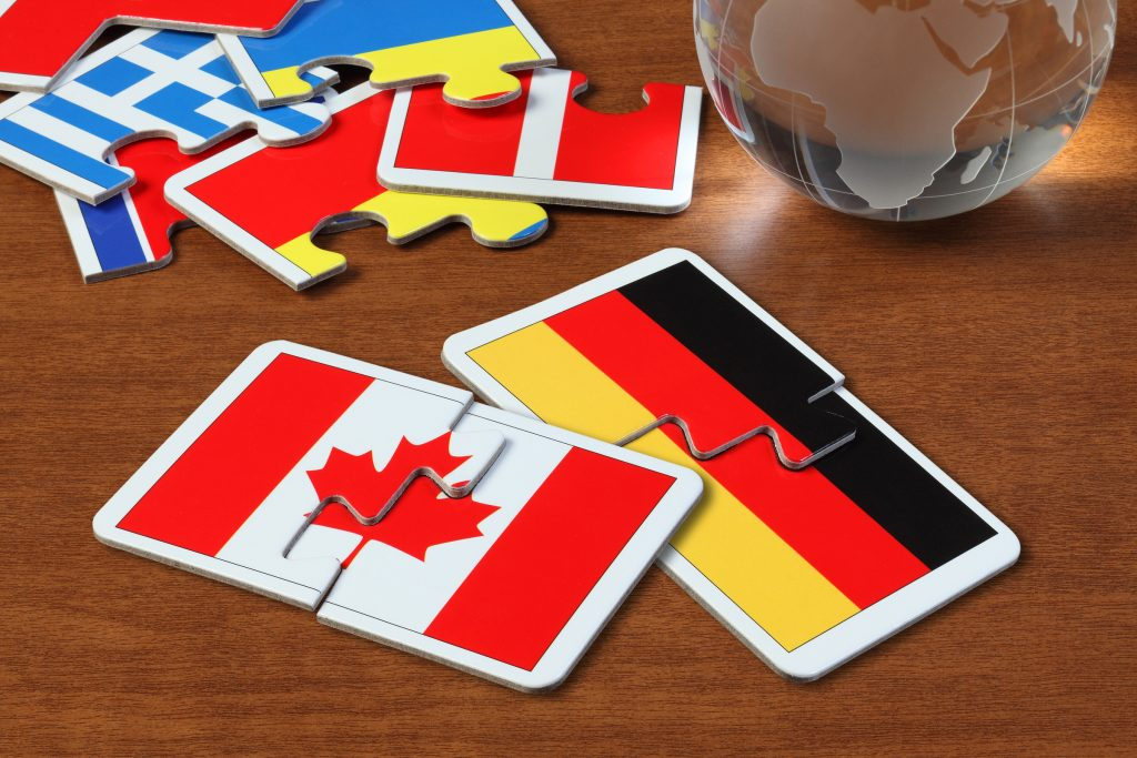 puzzle with the national flag of Canada and Germany on wooden table