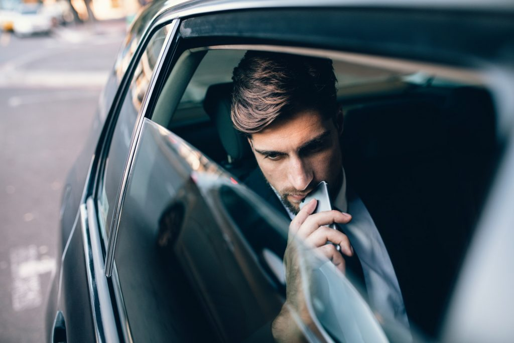 phone and thinking. Caucasian male business executive travelling by a cab.