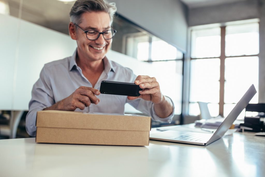 Smiling mid adult man taking scanning a delivery box on his desk. Man taking picture of a package.