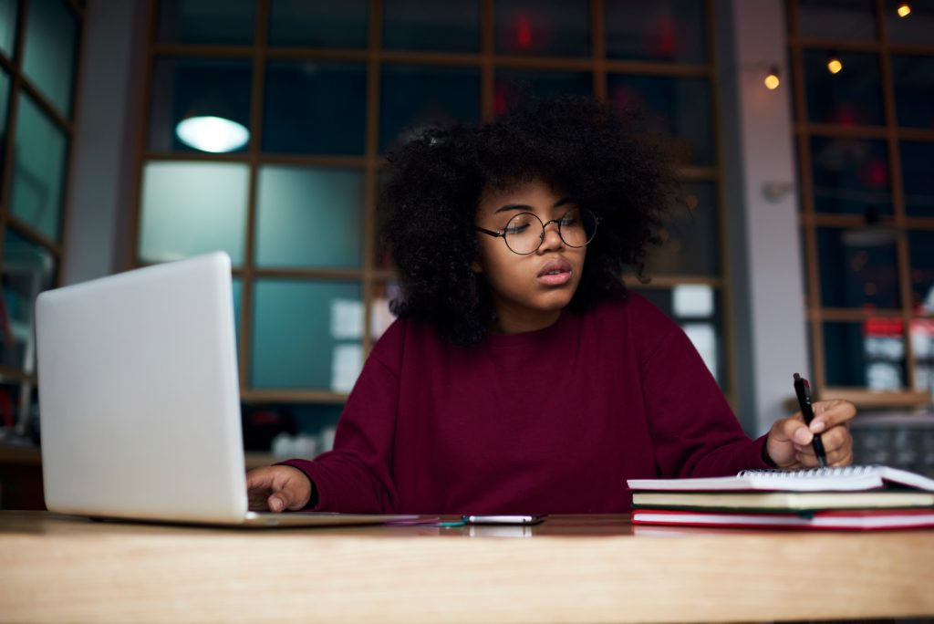 Concentrated young female student in glasses learning in university campus using laptop computer and wireless connection to internet preparing to examination, attractive hipster girl writing essay